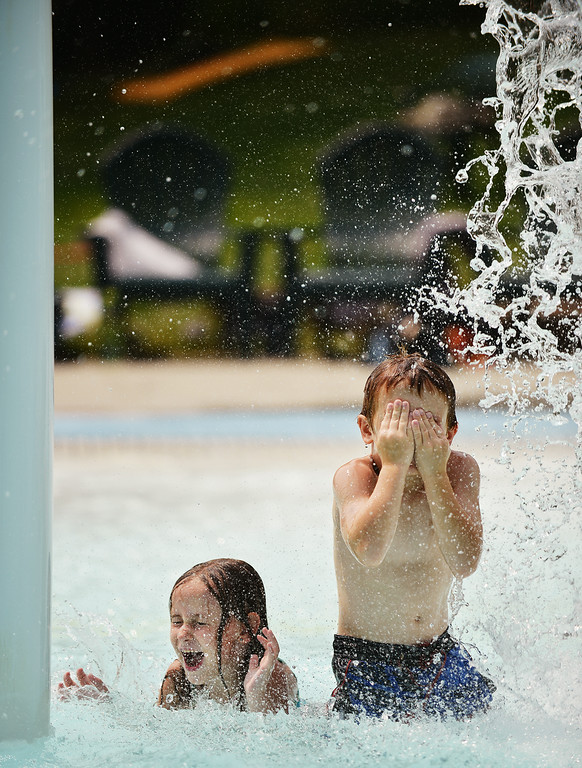 Six-year-old Hailey Lagwig, left, and Tristan Miller, 6, react as water from the tumble bucket spills down in the baby pool Thursday afternoon at Kendrick Pool. The Sheridan Press|Justin Sheely.