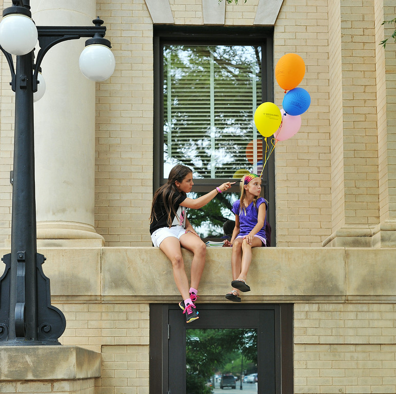 Eleven-year-old Aleyah Eisele, left, and Libby Franklin, 11, hang out on a window ledge on City Hall during the Third Thursday Street Festival on Grinell. The Sheridan Press|Justin Sheely.