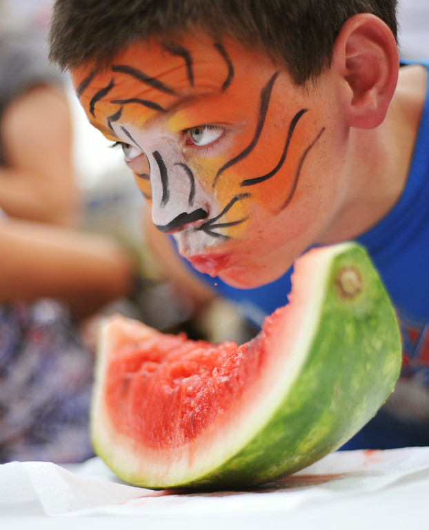 Eleven-year-old Ian Taylor checks on his competition in the watermelon-eating contest during the Third Thursday Street Festival on Main Street. The Sheridan Press|Justin Sheely.
