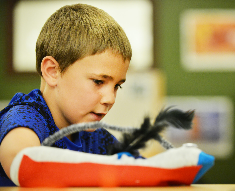 Kolby McDougall plays with his sock puppet during the 'Summer Bridges' summer school enrichment program Wednesday at Tongue River Elementary School in Ranchester. TRE students made puppet socks and learned how to manipulate stick puppets with string to perform a marionette puppet show. The Summer Bridges program is a state grant to fund summer school programs, which are geared towards a balance of remediation and enrichment.