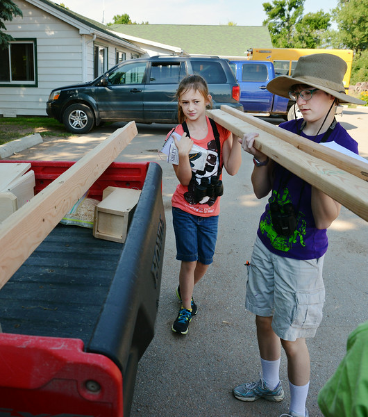 Ten-year-old Taylor Midthun, left, and teacher's assistant Katharine Mansfield, 13, set wood boards in the back of a ranger as the group prepares to install bird boxes during the Science Kids birding trip to the Padlock Ranch Thursday in Dayton. The boxes were installed to accommodate the declining American Kestrel Bird population. The students exercised birding skills and installed bird boxes on the ranch before hitting the Dayton Pool to beat the heat. The Sheridan Press|Justin Sheely.