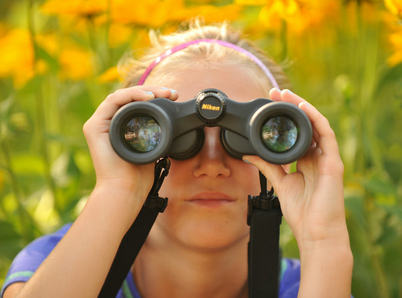 Eleven-year-old Aria Heyneman looks through a pair of binoculars during the Science Kids birding trip to the Padlock Ranch Thursday in Dayton. The students exercised birding skills and installed bird boxes on the ranch before hitting the Dayton Pool to beat the heat. The Sheridan Press|Justin Sheely.