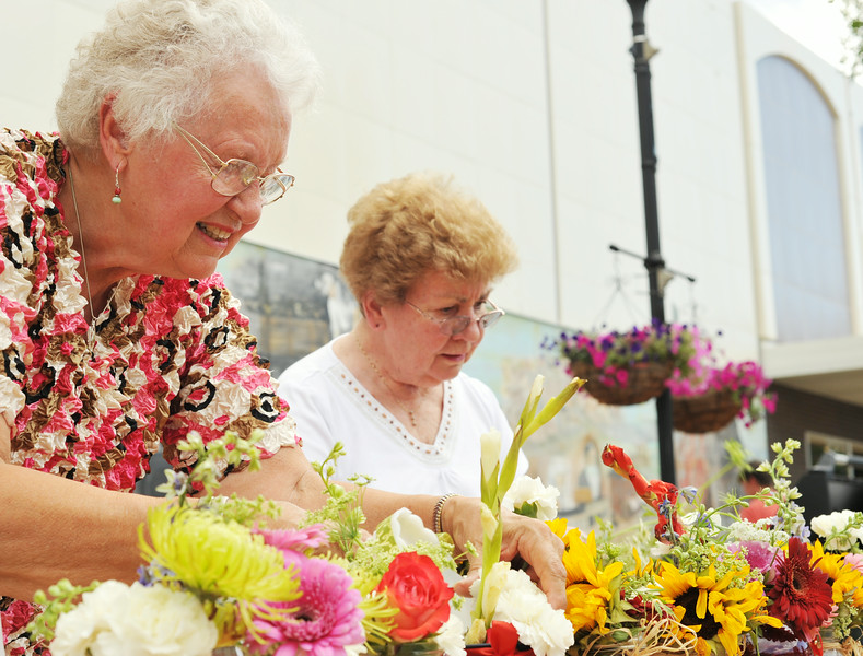 Donna Lee, left, and Elaine Guilford, both Past Queens of the Daughters of the Nile, prepare flower arrangements to sell for supporting the Shriners Hospitals for Children during the Farmers Market Thursday evening on Grinnell Street. The Farmers Market is held every Thursday from 5 p.m. to 7 p.m. on Grinnell Street through September. The Sheridan Press|Justin Sheely.