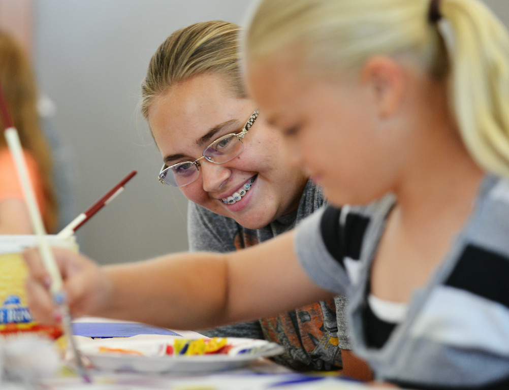 Fourteen-year-old Emma Manor, left, watches her sister Sarah Manor, 11, paint on a board during Kids' Art Camp Tuesday at Sagebrush Community Art Center inside the historic Train Depot. The painting class lead by local artist Sonja Caywood taught students how to turn random shapes into art. The Sheridan Press|Justin Sheely.
