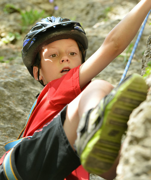 Eight-year-old Landis Zebroski finds a foothold during the K-LIFE rock climbing trip to Piney Creek Canyon in Story The trip was offered for free by K-LIFE for the youth–many of which had never climbed before. The Sheridan Press|Justin Sheely.