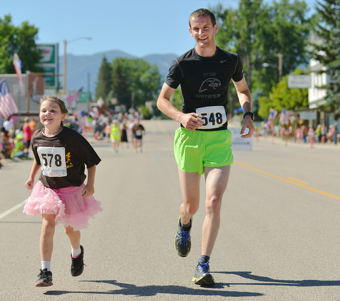 Eight-year-old Natalie Gilbert runs to the finish line with Cole Jolovich during the Dayton Days Mile Run Saturday morning on Main Street. Jolovich had finished comfortably in first place but immediately turned around to run along side with other runners on the home stretch to the finish line. Gilbert was one of the last to cross the finish line with Jolovich. The Sheridan Press|Justin Sheely.