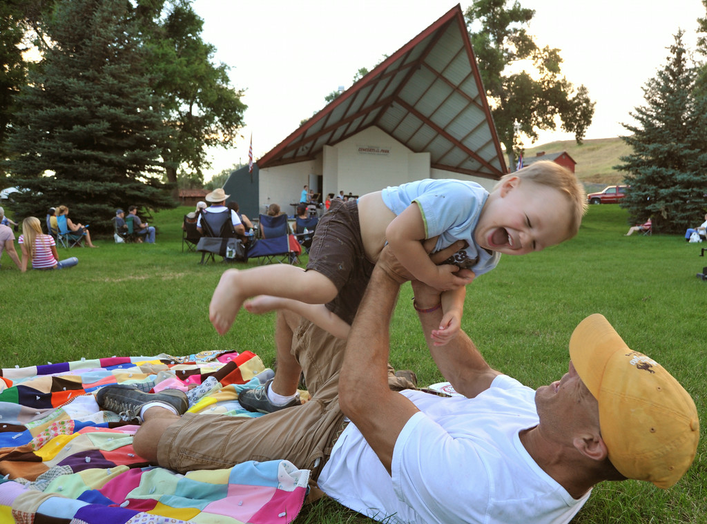 Two-year-old Henry Szewc laughs as Jason Szewc lifts him during the Concert in the Park performance by the Sheridan Concert Band Tuesday evening at Kendrick Park. The Sheridan Press|Justin Sheely.