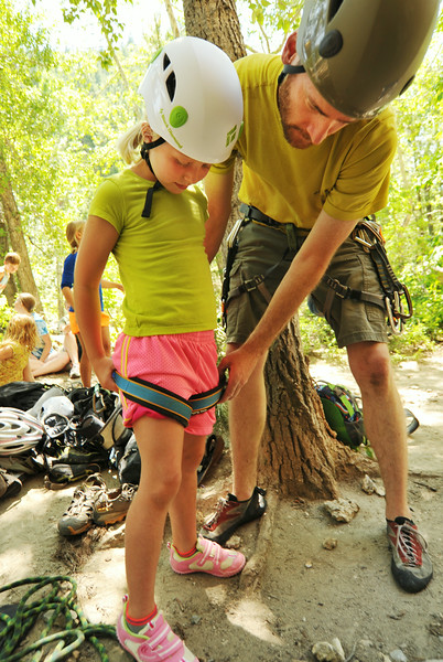 Eight-year-old Alyvia Cooper is helped into her junior climbing harness by Paul Graslie during the K-LIFE rock climbing trip to Piney Creek Canyon in Story. The trip was offered for free by K-LIFE for the youth–many of which had never climbed before. The Sheridan Press|Justin Sheely.