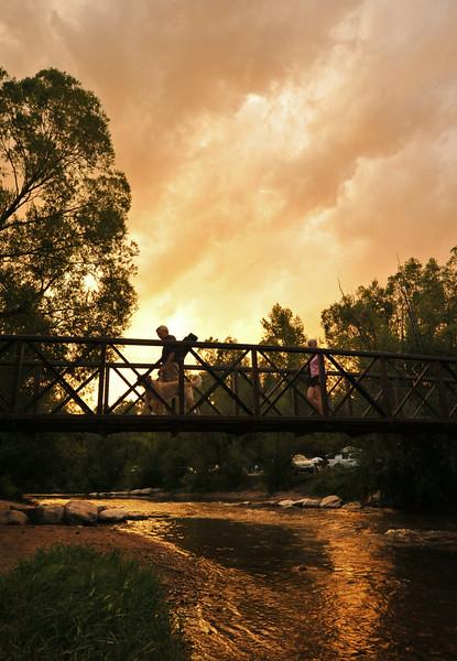 A couple of concertgoers cross the bridge over the Big Goose Creek as the sunset illuminates the sky Tuesday night at Kendrick Park. The Sheridan Press|Justin Sheely.