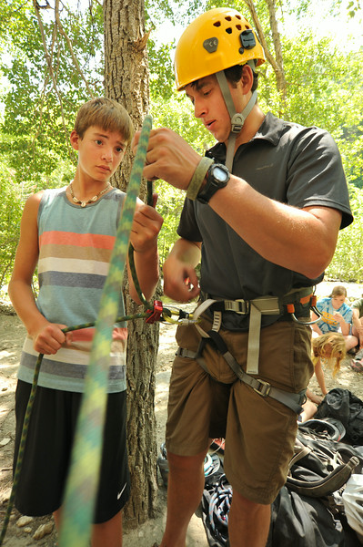Fourteen-year-old Samuel Walker, left, watches as Bret Riley explains the belay system during the K-LIFE rock climbing trip to Piney Creek Canyon in Story The trip was offered for free by K-LIFE for the youth–many of which had never climbed before. The Sheridan Press|Justin Sheely.