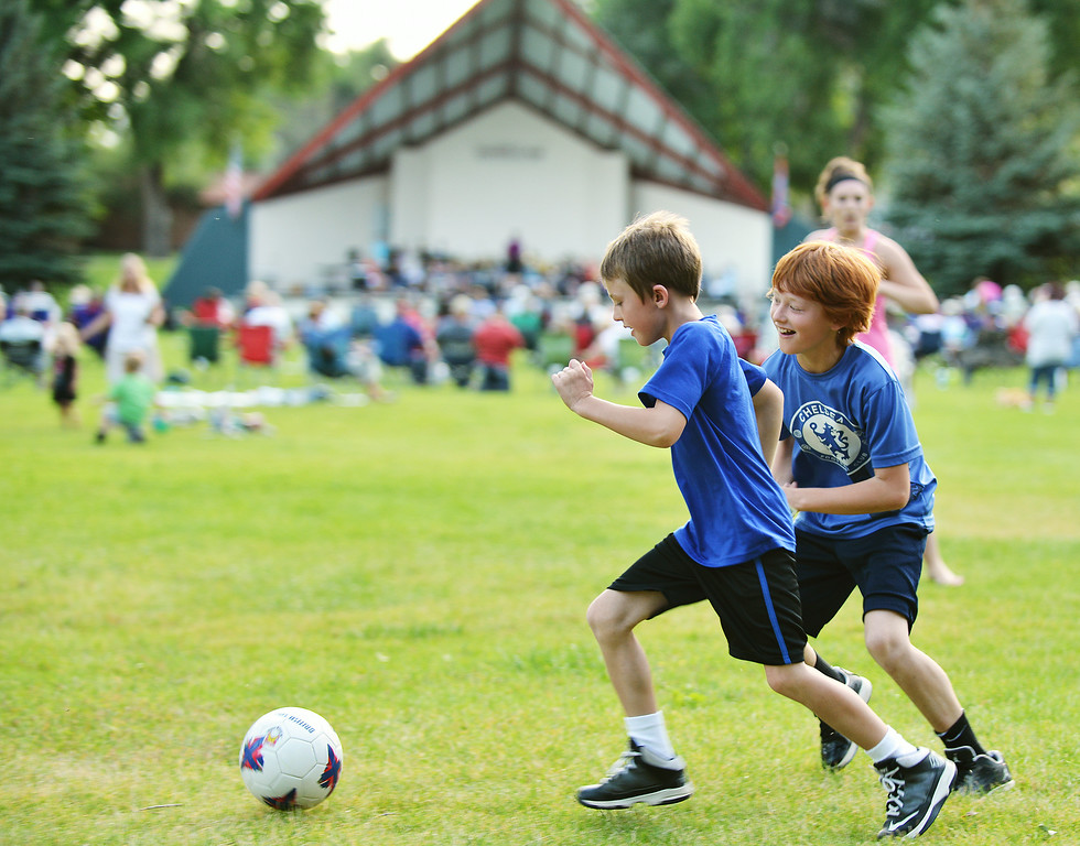 Eight-year-old Bridger Mortensen, left, and brother Brennan Mortensen, 10, play soccer with friends on the far side of the field during the Concert in the Park performance by the Sheridan Concert Band Tuesday evening at Kendrick Park. The Sheridan Press|Justin Sheely.