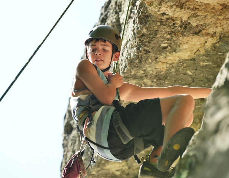 Fourteen-year-old Samuel Walker hangs on the rope for a breather before continuing his climb during the K-LIFE rock climbing trip to Piney Creek Canyon in Story The trip was offered for free by K-LIFE for the youth–many of which had never climbed before. The Sheridan Press|Justin Sheely.