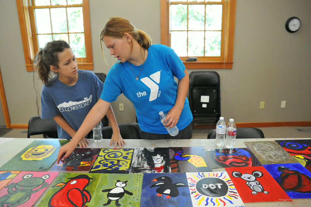 Twelve-year-old McKenna Arndt, left, and Soul Nelson, 13, look over the finished acrylic paintings during Kids' Art Camp Tuesday at Sagebrush Community Art Center inside the historic Train Depot. The painting class lead by local artist Sonja Caywood taught students how to turn random shapes into art. The Sheridan Press|Justin Sheely.
