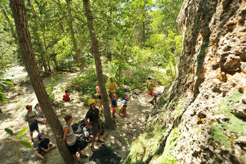 A climber descends the rock face as the group watches during the K-LIFE rock climbing trip to Piney Creek Canyon in Story. The trip was offered for free by K-LIFE for the youth–many of which had never climbed before. The Sheridan Press|Justin Sheely.