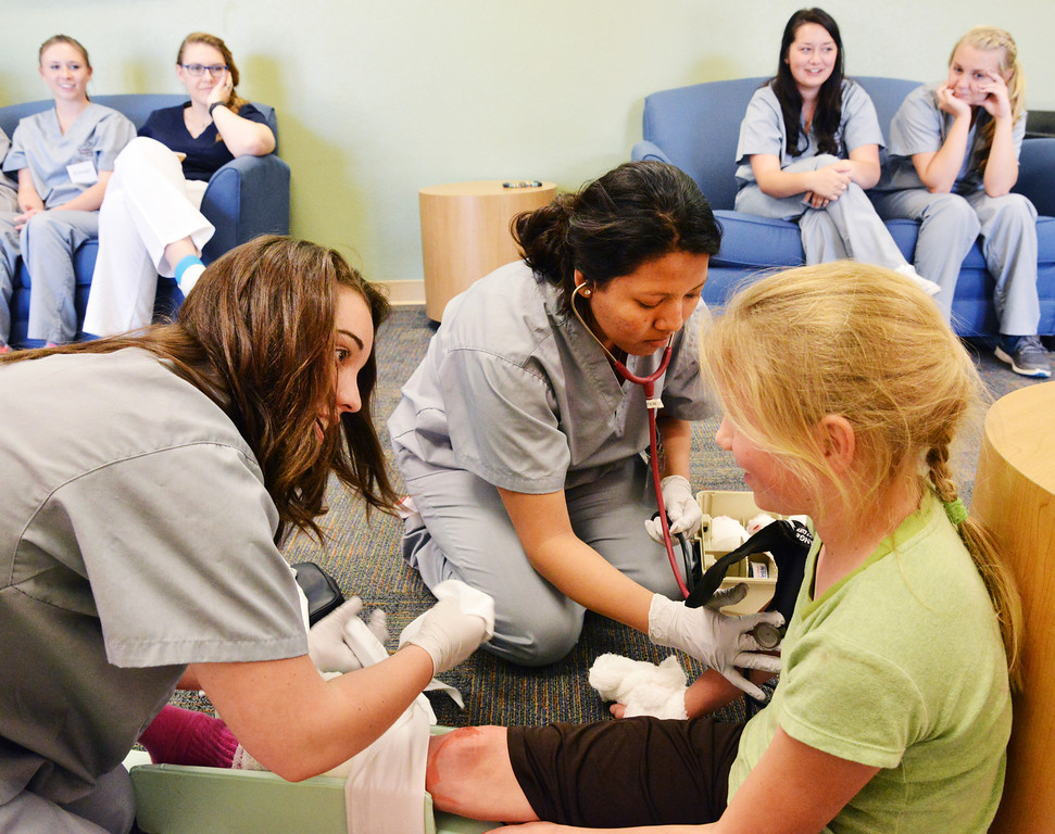 High School junior Sarah Burton of Gillette, left, and Cindy Alvaerz, a Sheridan junior, work on dressing wounds on fifth grader Elaine Charlson for a life scenario simulation during the 'Dream Big…Be a Nurse' high school nursing camp Wednesday at the Sheridan College Wyoming Simulation Center. Charlson had red paint and a deer antler taped to her leg to resemble a leg injury from a long boarding accident. The high school nursing students practiced their skills to talk to the patient, identify injuries and dress them.