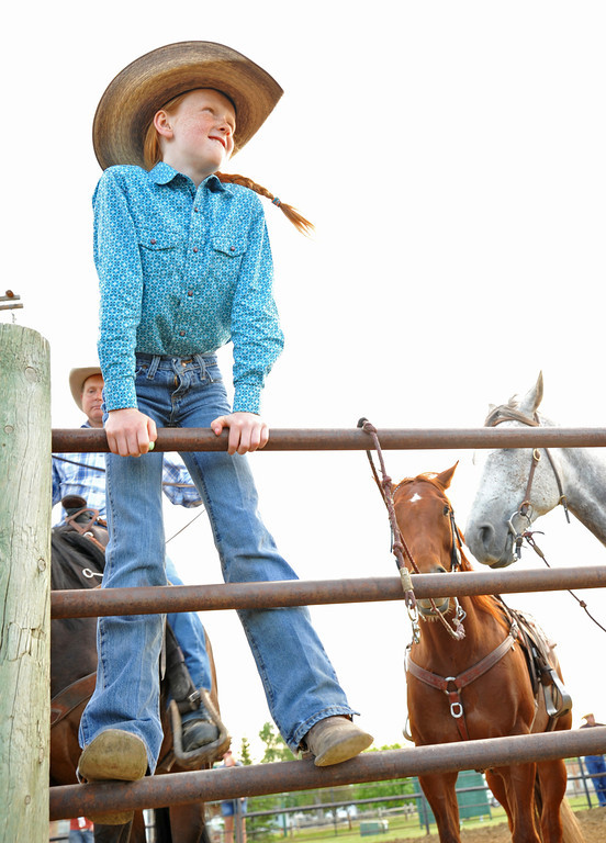 Eight-year-old Grace Peterson of Buffalo stands on the fence as she waits for her turn at barrel racing during the Sheridan Cowgirls Association Rodeo Thursday evening at the Sheridan County Fairgrounds.