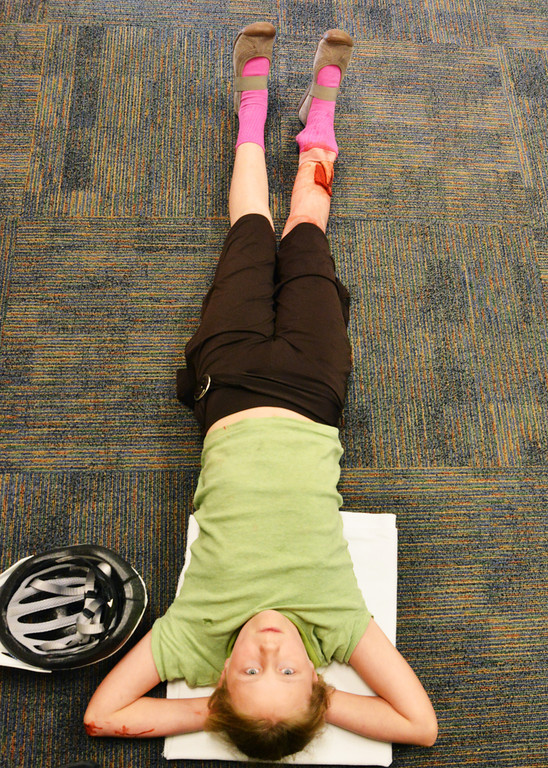 Fifth grader Elaine Charlson rests on the floor as a group of nursing students discuss their training for a life scenario simulation during the 'Dream Big…Be a Nurse' high school nursing camp Wednesday at the Sheridan College Wyoming Simulation Center. The youth had red paint and a deer antler taped to her leg to resemble a leg injury from a long boarding accident. The high school nursing students practiced their skills to talk to the patient, identify injuries and dress them.