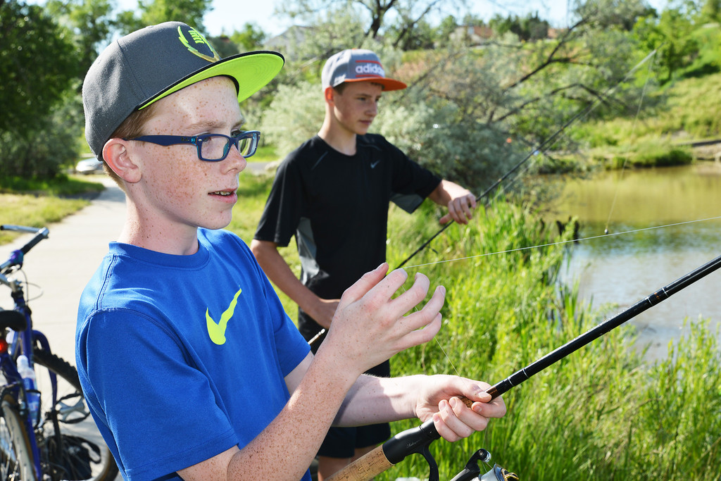 Fourteen-year-old Jarrod Roberts, left, and friend Hayden Burgess, 13, cast at Sam Mavrakis Pond off 8th Street Wednesday afternoon. The pond is a popular spot for Sheridan residents, young and old, to cast for fish.