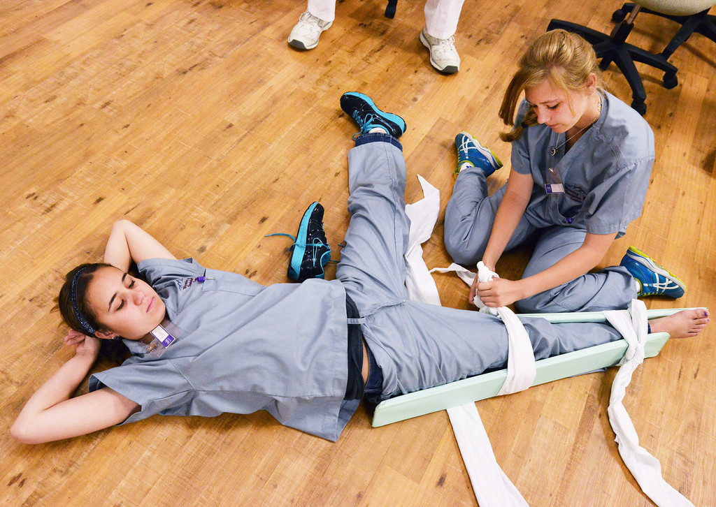 High school juniors Bailey Guernsey relaxes on the floor as Kaleigh Anderson dresses a leg splint during the 'Dream Big…Be a Nurse' High School Summer Camp last week at the Sheridan College Wyoming Simulation Center.