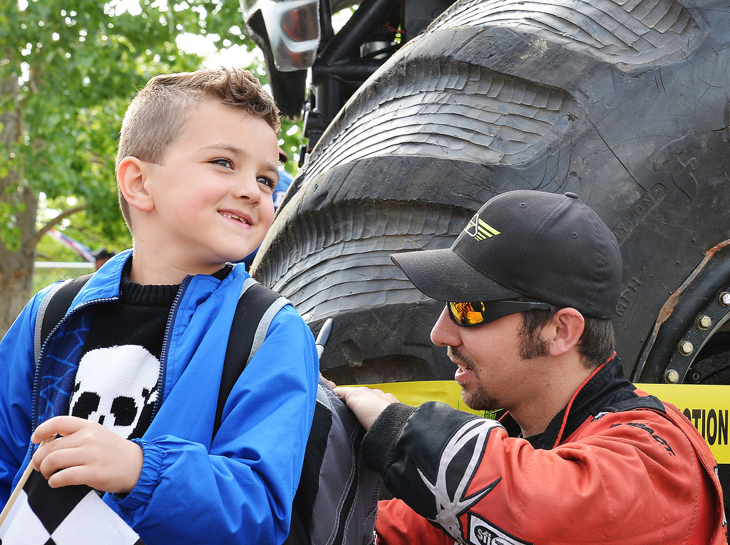 Monster truck driver Nate Circhner of Minnesota autographs six-year-old Michael Odom's backpack prior to the Mega Promotions Tour Monster Truck Show Saturday night at the Sheridan County Fairgrounds arena.