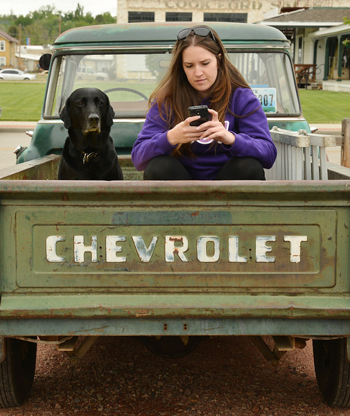 Kaycee Dube sits with her dog Duesenberg in the back of a 1957 Chevrolet pickup truck during the 'Cool Rides in a Cow Town' car show Saturday at Rails.