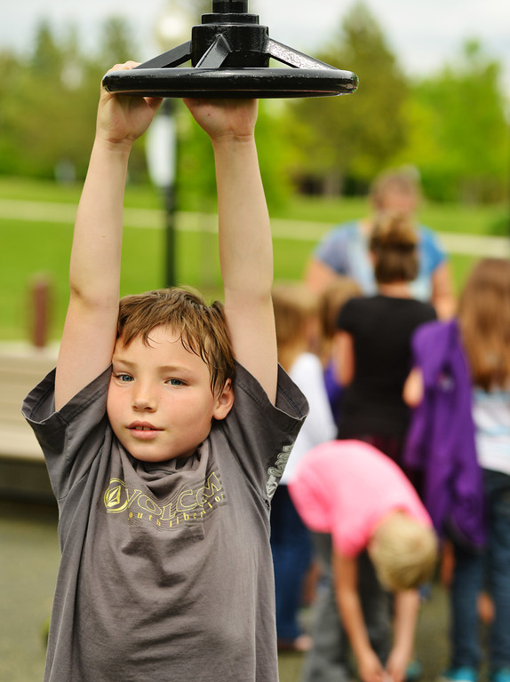 Eight-year-old Drake Dixon hangs from a piece of the playground equipment as the Great Foundations Center children gather up Tuesday afternoon at Whitney Commons.