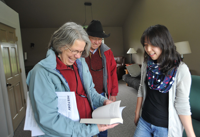 """Susie Cannon, left, and Kim Cannon look through resident writer Cathrine Chung's novel """"Forgotten Country"""" during the the Open Studios tour Saturday at the Ucross Foundation. Chung, who is from New York City, was finalizing her second novel during her stay at the Ucross Foundation residency program."""