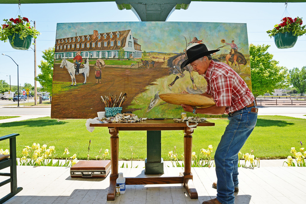 Western artist CR Sadler restores his original art piece of the historic Sheridan Inn Thursday morning on the front porch of the Sheridan Inn. Sadler offered to clean and retouch the painting he had been commissioned back in 1990 by the previous inn owners. Sadler donated his time in the restoration of the painting, which will be hung in the historic site.
