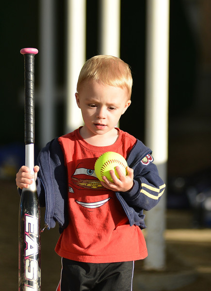 Three-year-old Camdin Miles plays with a bat and softball found in the dugout during Women's League Softball Wednesday evening in the Softball Complex at Sheridan College.