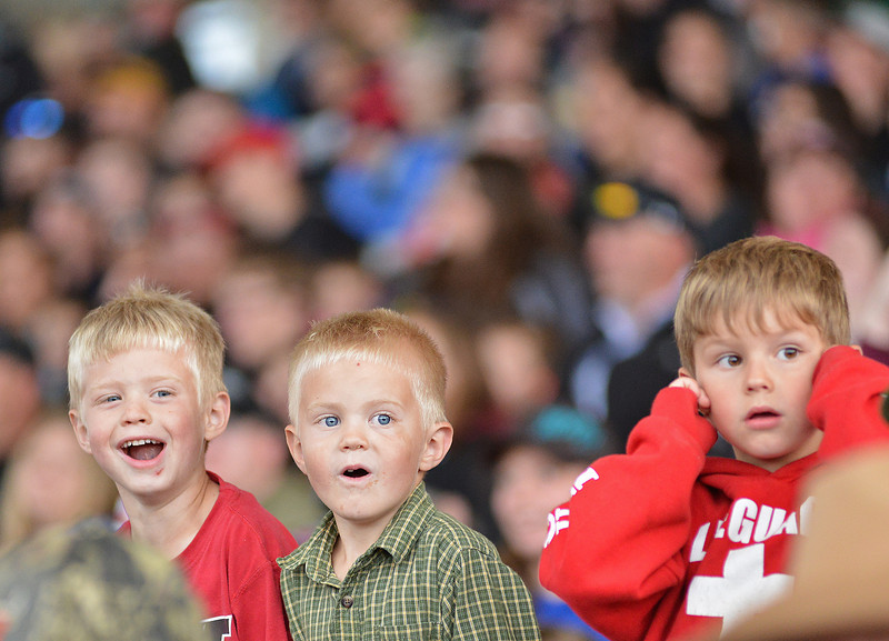Willie Morris, Luke Morris, and Sam Wilcock, from left to right, react as the monster trucks enter the arena during the Mega Promotions Tour Monster Truck Show Saturday night at the Sheridan County Fairgrounds arena.