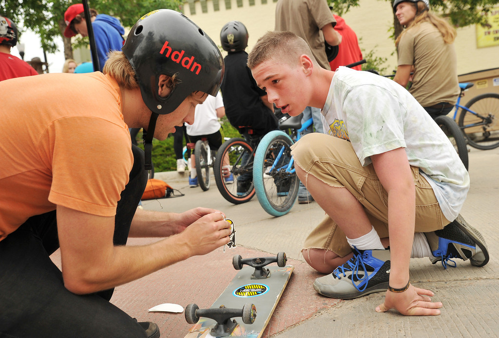Skate Church member Josh Jost peels a skateboard decal for fourteen-year-old Kyle Biggs during the 'Sheridan Takeover' free skate clinic Saturday afternoon on Grinnell Plaza. The event was to be a positive influence for Sheridan youth and to teach new bike and skateboard tricks. The events were sponsored by The Sports Stop, Sheridan K-Life, and local churches.