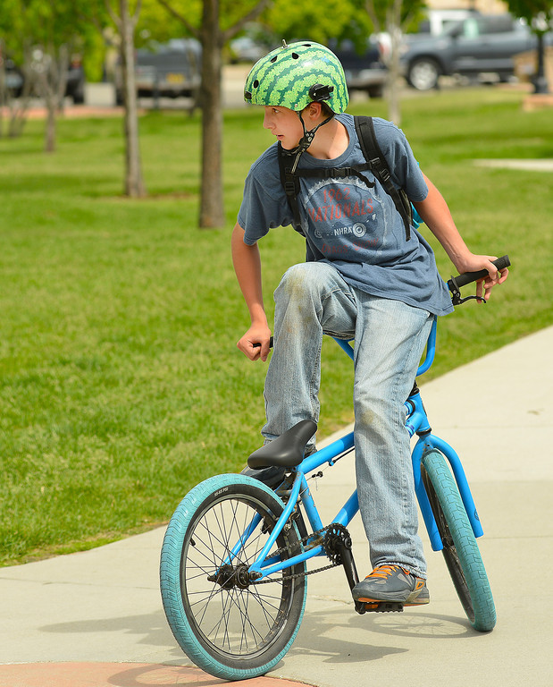 Fourteen-year-old Blaine Buszkiwic sits on the handlebars of his bike as he rides around Whitney Commons Tuesday afternoon. Buszkiwic was on his way to the Skate Park with his friends.
