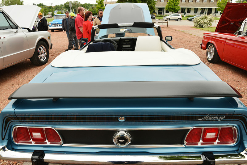 Guests look at a 1973 Ford Mustang convertible during the 'Cool Rides in a Cow Town' car show Saturday at Rails.