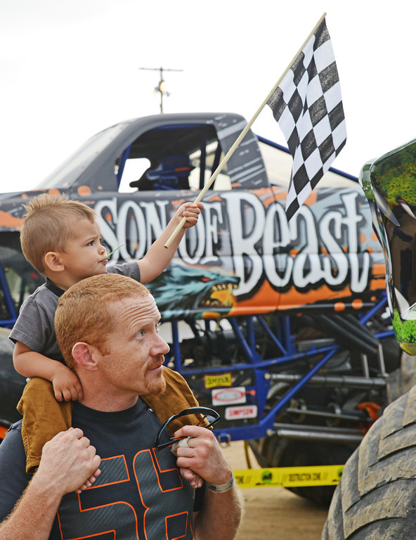 John Stewart and two-year-old Jaxon Anderson look at 'Tail Gator' monster truck prior to the Mega Promotions Tour Monster Truck Show Saturday night at the Sheridan County Fairgrounds arena.