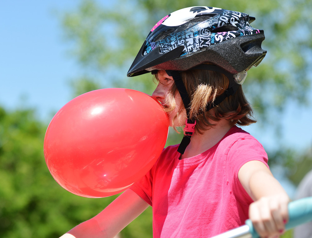 Fourth grader Jacy Luckjohn holds a balloon with her teeth as she rides her bike home after the early dismissal on the last day of School Thursday at Tongue River Elementary School.
