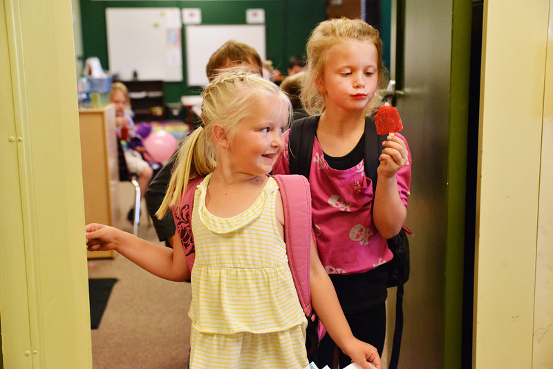 Kindergarteners Joni Simonson, left, and Chaney Reish wait at the door of their classroom before the early dismissal on the last day of School Thursday at Tongue River Elementary School.