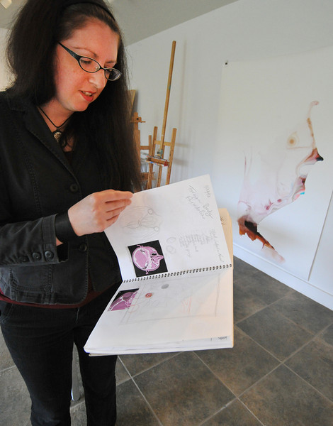 """Resident artist Vesna Jovanovic of Chicago, Ill., shows sketchings from her book that she used to compile her ideas for the series """"Foreign Bodies"""" during the Open Studios tour Saturday at the Ucross Foundation. Jovanovic's work is a combination of pencil and ink on a material called yupo."""