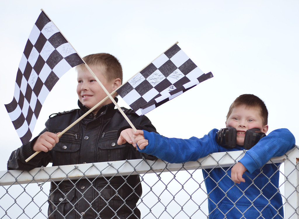Ten-year-old JW Fort, left, and six-year-old brother Lane Fort wave their autographed flags as the monster truck drivers get ready during the Mega Promotions Tour Monster Truck Show Saturday night at the Sheridan County Fairgrounds arena.