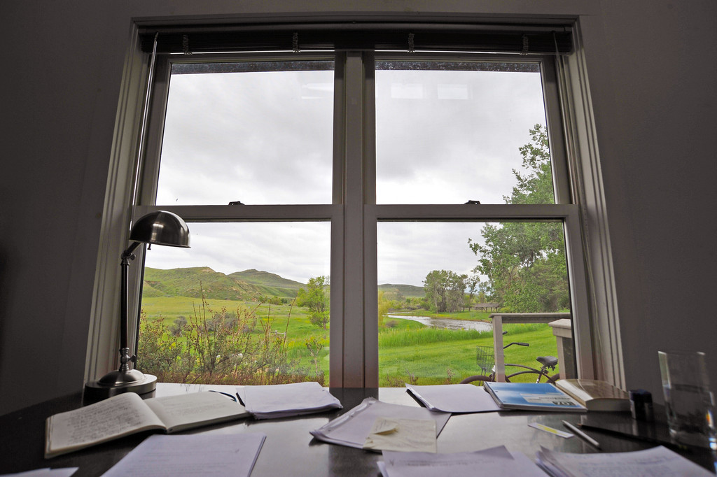 Green grass and a calm river serves a view for a Ucross Foundation author's writing desk during the tour at the Ucross Foundation. The writer's house, like many of the other residents' studios, features rooms with inspirational views of the country.