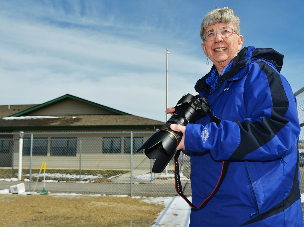 Cel Hope holds her camera as a volunteer exercises a dog outside the Dog and Cat Shelter on Wednesday. Hope photographs the animals at the shelter for the website and to help the adoption process. Hope will be leaving her role as Director of the Sheridan Dog and Cat Shelter this April 1.