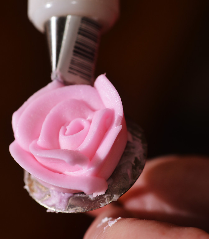 Marla Garriffa uses a flower tip on a bag of frosting to form a decorative rose for the cake.