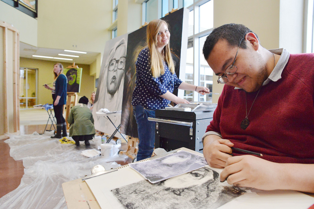 "Emily reed looks over at Tyshon Bird as he works on a charcoal drawing of a bear's face over his self portrait during ""Reflections on Reflection"" Saturday afternoon at the Sheridan College Edward A. Whitney Academic Center atrium. The event featured student-lead interdisciplinary arts from the Sheridan College Art House, which included the Theater Department, Art Department and Music Department to interpret Shel Silverstein's poem ""Reflection."" The college students collaborated with high school students from Sheridan High School, Fort Mackenzie, and Big Horn High School for the performance."