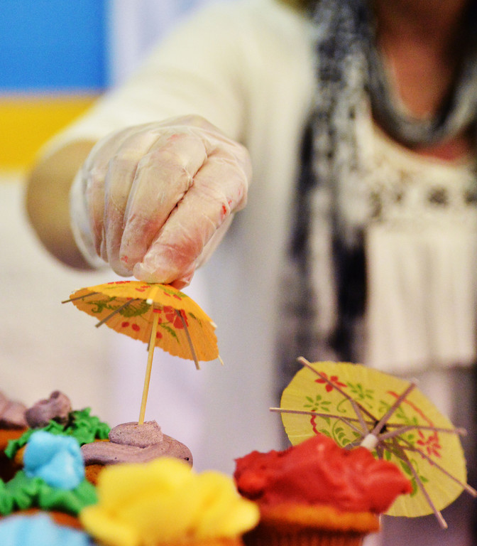 Novelty umbrellas are placed on cupcakes during preparation for the Festival of Cultures Friday at the Sheridan College Golden Dome.