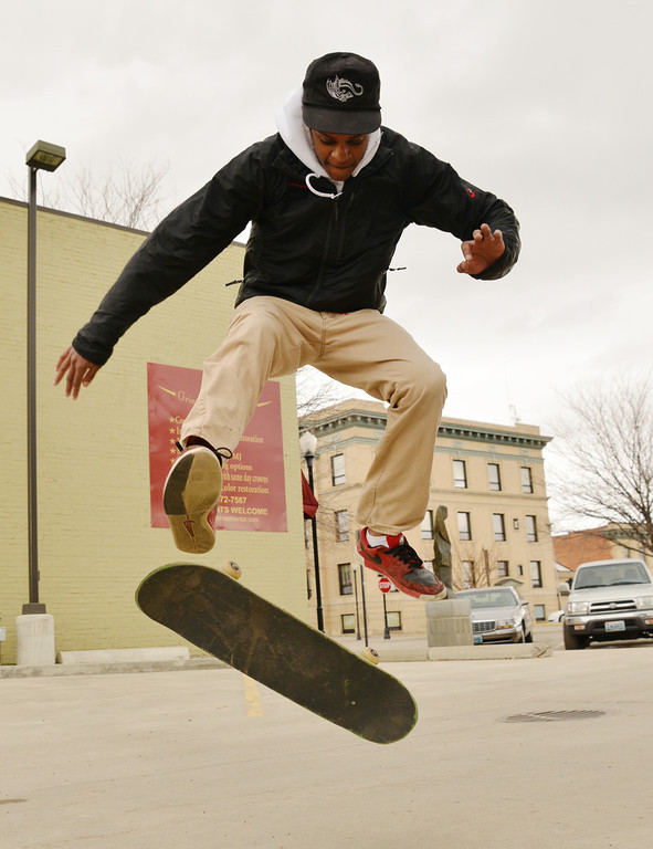 Malik Grant does a kick flip on his skateboard Thursday afternoon at the Sheridan Press parking lot.