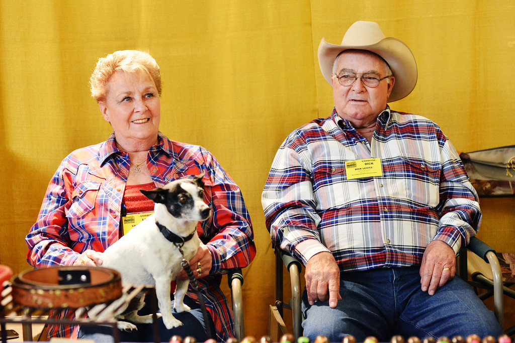 Lillie and Dick Levitz of Utah sit with their dog Buster behind their booth as visitors walk by during the annual Leather Crafters Trade Show Friday at the Holliday Inn Convention Center. The Levitz say that everyone who visits their booth always ask about Buster if he isn't present.