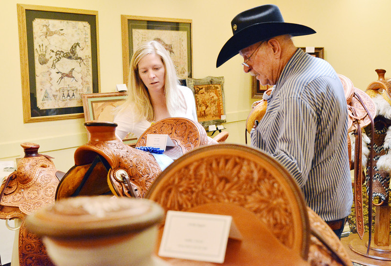 Kristen King of Sheridan, left, and Jerry Hutcherson of Colorado look through the selection of saddles that were in the competition during the annual Leather Crafters Trade Show Friday at the Holliday Inn Convention Center.