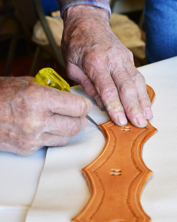 A leather instructor makes reference marks for a layer of soft leather in a chaps-making workshop Tuesday during the Leather Crafters convention at the Holiday Inn.