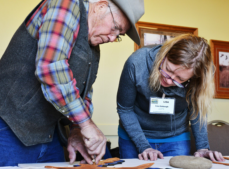Colorado man Jesse Smith makes a hole in the layers of leather for tracing reference as student Lisa Eshbaugh of Bozeman, Mont., watches intently in a chaps-making workshop Tuesday during the Leather Crafters convention at the Holiday Inn.