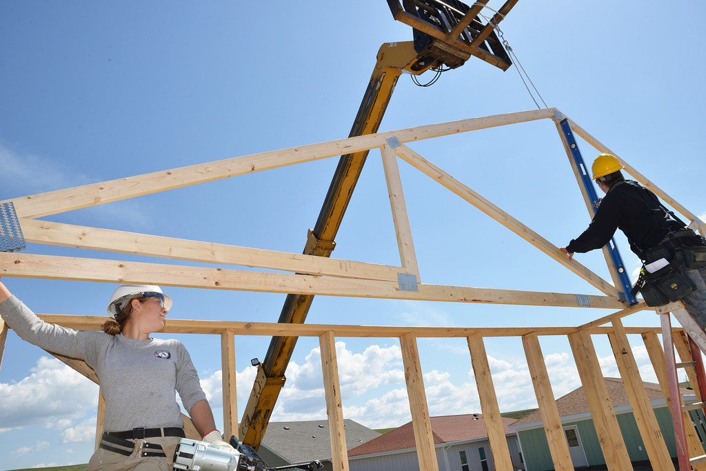 Rebekah Tatkovsky of the NCCC Americorps, left, holds a roofing truss on the mark at it is flushed out on the other side at the Habitat for Humanity home Wednesday at the Poplar Groove subdivision.
