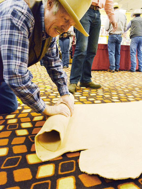 Don Bradshaw of Clearfield, Utah, rolls up a roll of leather saddle skirting after inspection at a vendor's booth during the annual Leather Crafters Trade Show Friday at the Holliday Inn Convention Center.